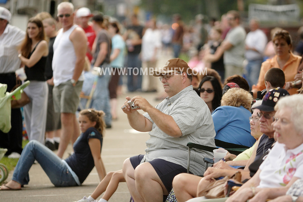 Middletown, N.Y. - Spectators, including a man s with a small digital camera, line Highland Avenue to watch the Middletown Fire Department's 147th Anniversary Fire Parade on Sept. 9, 2006. ©Tom Bushey