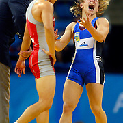Irini Merleni of the Ukraine reacted to the judge's decision to award her the gold medal over her opponent, Chiharu Icho of Japan, center, in the women's freestyle 48kg gold medal match at Ano Liossia Hall during the 2004 Summer Olympic Games in Athens, Greece. The opponents were tied at 2-2 with the judge's decision going to Merleni.