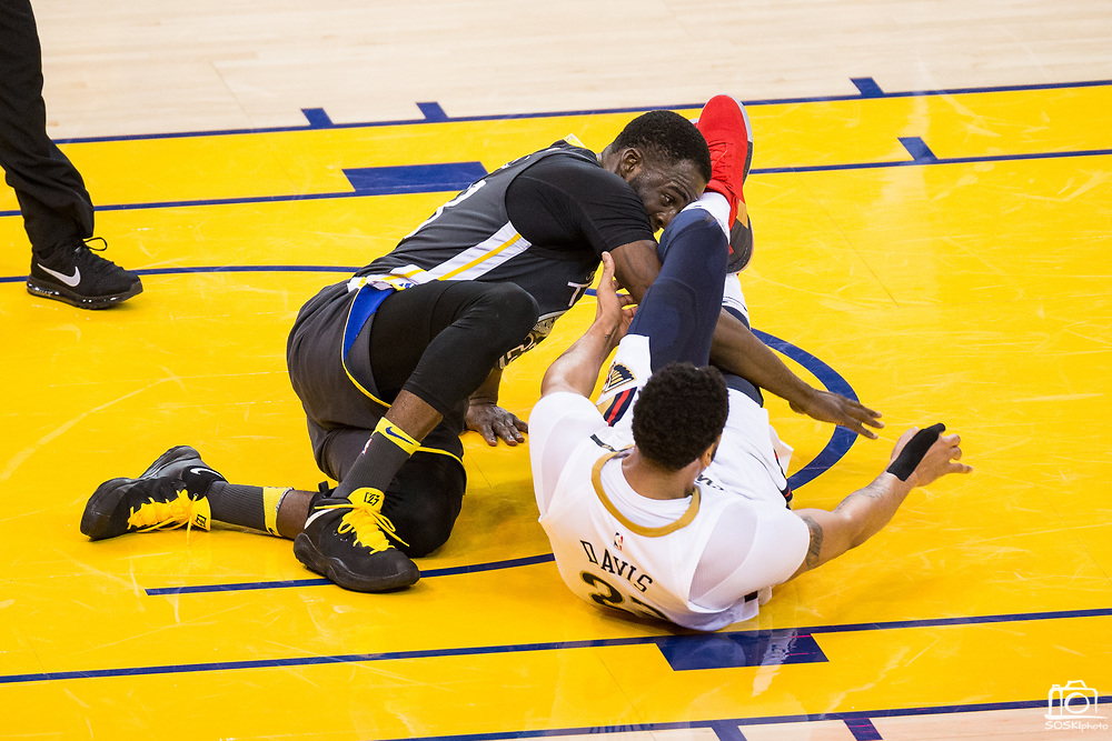 Golden State Warriors forward Draymond Green (23) and New Orleans Pelicans forward Anthony Davis (23) get tangled up on the floor at Oracle Arena during Game 2 of the Western Semifinals in Oakland, California, on May 1, 2018. (Stan Olszewski/Special to S.F. Examiner)