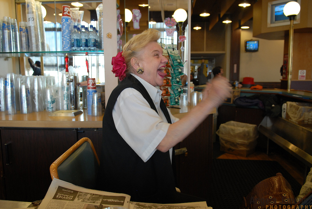"Diane Smith, a long-time bartender at the Man O' War room at the Aqueduct race track in New York City, watches her horse, the #2, win a race on February 16, 2007. She says she likes horses with even numbers, and those with the words Saint, Dixie or Smoking in their names. ""I'm always getting in trouble for smoking,"" she says. ..Betting on the horses is still a popular game and the money still flows, but off track betting and other forms of entertainment have eroded live attendance at the races.  The daily diehard betters and horse lovers who sparsely populate the place on work days are joined by a bigger crowd on the weekends. ..The Aqueduct, located in Ozone Park, Queens, is the only horse racing track in New York City and probably the coldest in the country (most of the others are in Kentucky, Florida or California). Horses race on the winterized inner dirt rack from January 1st through the end of April. Aqueduct was built in 1894, renovated in 1959, then opened for winter racing in 1975. It is the winter race track operated by the New York Racing Association (NYRA), which also runs Belmont and Saratoga in the warm seasons. Betters at Aqueduct watch and bet on the nine daily live races and all other races around the country via Simulcast. .."