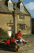 Two women country walkers stop on their day's trek across the Cotswolds in the village of Stanton.