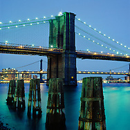 The Brooklyn Bridge at night as seen from the South Street Seaport in New York City.