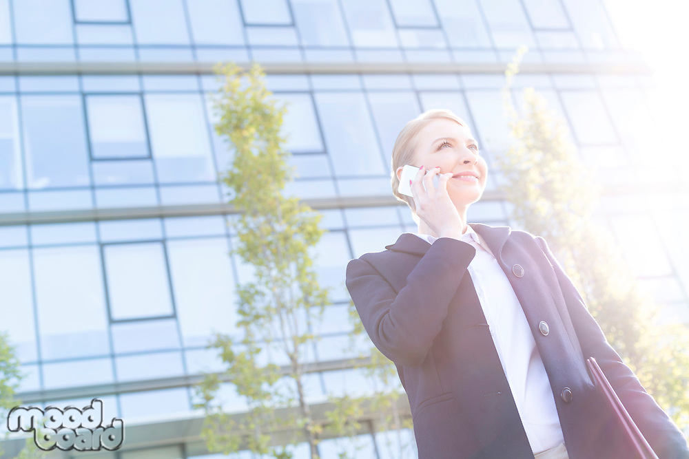 Low angle view of smiling businesswoman using cell phone on sunny day