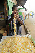 A grain seller with corn at his street front stall in Likoni, Kenya.