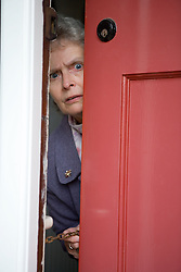 Older woman looking through door using a safety chain,
