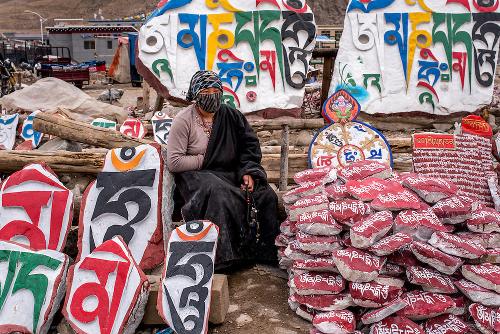 A vendor sells mani stones inscribed with mantras near the Gyanak mani wall in Yushu prefecture, Tibet (Qinghai, China).