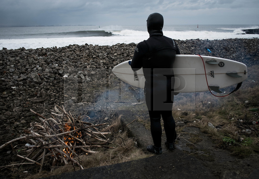 © Licensed to London News Pictures. 18/01/2014<br /> <br /> Teesside, England<br /> <br /> Surfer Mick Jackson stands next to a fire and watches the waves breaking after surfing on the North east coast of England.<br /> <br /> Photo credit : Ian Forsyth/LNP