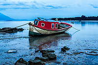Barco encalhado na areia durante a maré baixa na Praia do Ribeirão da Ilha ao anoitecer. Florianópolis, Santa Catarina, Brasil. / Boat stranded on the beach during low tide at Ribeirao da Ilha Beach at dusk. Florianopolis, Santa Catarina, Brazil.