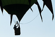 A hot air balloon pilot reaches for his burner during the Great Reno Balloon Race Preview Day on Thursday, September 7, 2017. Balloons stage at Rancho San Rafael Regional Park just a few miles north of downtown Reno, Nevada, and the three day event officially kicks off on Friday, September 8.<br /> <br /> The Great Reno Balloon Race is the largest free hot-air ballooning event in the world. An average of 120,000 spectators attend the event each year.