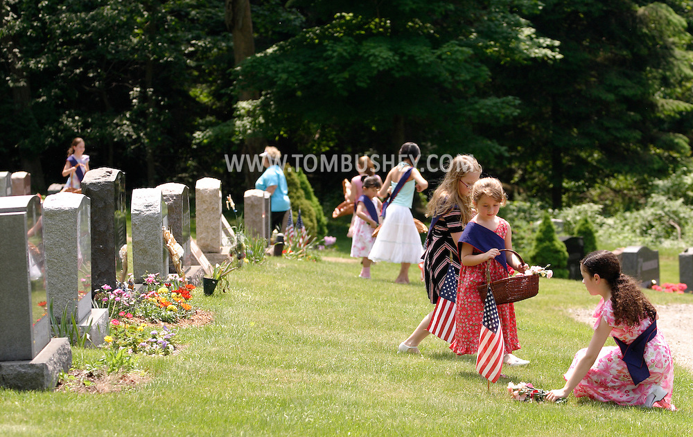 Hamptonburgh, N.Y. - Young girls place flowers on a veterans' graves during a Memorial Day services at Hamptonburgh Cemetery on May 29, 2006. ©Tom Bushey