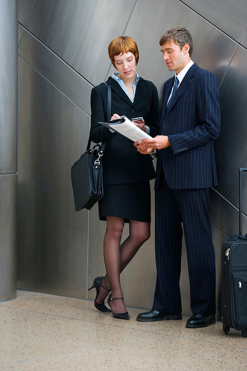A late 20's Caucasian business woman and a early 30's Caucasian business man in an airport with their luggage discuss something while looking at a report and notes on her PDA..20050916_MR_C.20050916_MR_D.20050916_PR_A