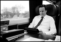 The Prime Minister David Cameron working on the train on the way to Swansea, Wales, to deliver a speech, Friday April 1, 2011, The Prime Minister is going to receive a personalised iPad app to help him stay on top of Government business.  Photo By Andrew Parsons/ i-Images..Full Byline Mandatory