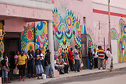 People wait for jitney buses in front of a wall mural in downtown Nassau, Bahamas.
