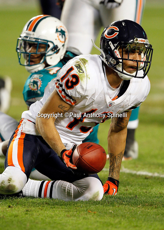 Chicago Bears wide receiver Johnny Knox (13) comes up with grass in his face mask after catching a first quarter pass and getting gang tackled by Miami Dolphins linebacker Channing Crowder (52) and Miami Dolphins cornerback Sean Smith (24) during the NFL week 11 football game against the Miami Dolphins on Thursday, November 18, 2010 in Miami Gardens, Florida. The Bears won the game 16-0. (©Paul Anthony Spinelli)