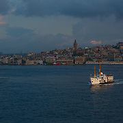 A boat on the Bosphorus Strait at sunrise with the view of the Asian side of Istanbul in the background.