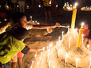 26 DECEMBER 2014 - PATONG, PHUKET, THAILAND:  Thai children light candles for victims of the 2004 tsunami on Patong Beach in Patong, Phuket. Hundreds of people died in Patong and nearly 5400 people died on Thailand's Andaman during the 2004 Indian Ocean Tsunami that was spawned by an undersea earthquake off the Indonesian coast on Dec 26, 2004. In Thailand, many of the dead were tourists from Europe. More than 250,000 people were killed throughout the region, from Thailand to Kenya. There are memorial services across the Thai Andaman coast this weekend.     PHOTO BY JACK KURTZ