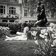 Woman reading a book while sunbathing amongst the flowers in the garden in front of the Theatre in Bergen centrum