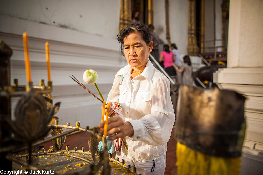 """01 JANUARY 2013 - BANGKOK, THAILAND:   A woman lights candles to make merit during a New Year's Day merit making service at Wat Suthat in Bangkok. Many Thais go to Buddhist temples and shrines to """"make merit"""" for the New Year. The traditional Thai New Year is based on the lunar calender and is celebrated in April, but the Gregorian New Year is celebrated throughout the Kingdom.    PHOTO BY JACK KURTZ"""