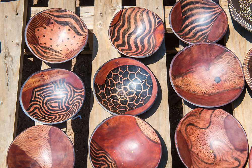 Table of handcrafted wooden bowls that are for sale in outdoor marketplace, Chobe National Park - Botswana