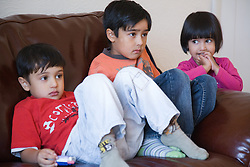 Three children sitting at home watching television together,