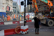 Digger drives past footpath disruption sign using illustration of TFL workman.