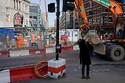 Digger drives past footpath disruption sign using illustration of TFL workman.