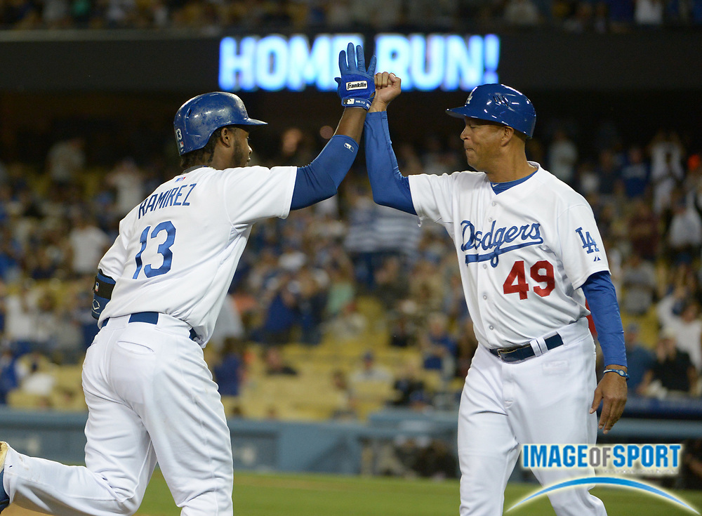 Apr 6, 2014; Los Angeles, CA, USA; Los Angeles Dodgers shortstop Hanley Ramirez (13) is greeted by third base coach Lorenzo Bundy (49) after hitting a home run in the eighth inning against the San Francisco Giants at Dodger Stadium. Ramirez hit two home runs in the Dodgers 6-2 victory.
