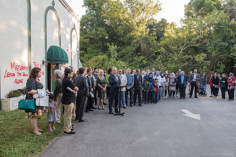 Supporters of the Louisville Islamic Center on River Road stand behind Mayor Greg Fischer as he speaks to media about graffiti found on the mosque when they arrived for a 7:30 prayer meeting Wednesday night. Sep. 17, 2015