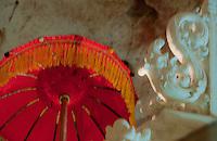 Red ceremonial umbrella inside the cave temple complex at Goa Giri Putri on Nusa Penida, Bali, Indonesia