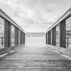 Pensacola Beach Florida wooden walkway beach access entrance black and white photo. Pensacola Beach is on Santa Rosa Island in the Emerald Coast region of the Southeastern United States. Photo is high resolution. Copyright ⓒ 2018 Paul Velgos with All Rights Reserved.