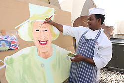 © Licensed to London News Pictures. 29/05/2012, Lashkar Gah, Afghanistan. A chef working for the British military in Afghanistan puts the finishing touches to a portrait of the Queen as he prepares decorations for a street party in the military base.  Photo credit : Alison Baskerville