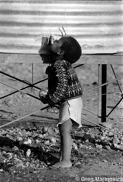A child tries to get a drink of water from a communal watertap in the Zevenfontein squatter camp north of Johannesburg, 15, July, 1992, South Africa. (Photo by Greg Marinovich)