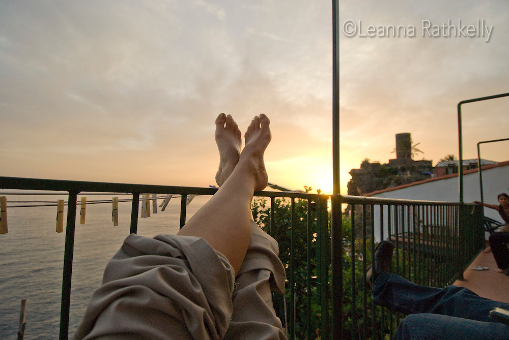 I relax with my feet up, as the sun sets over the Mediterranean in Vernazza, Cinque Terre, Italy.