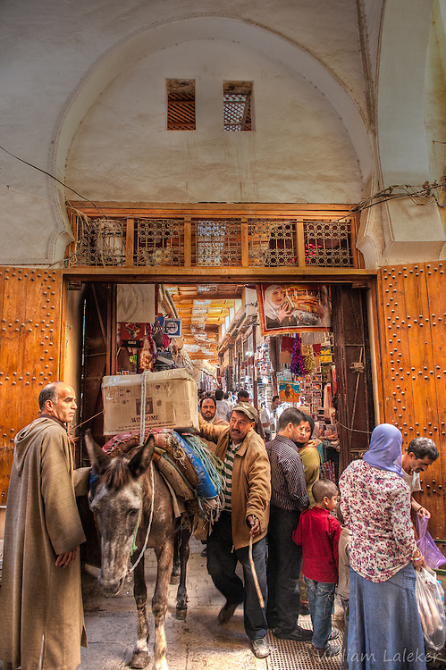 People and animals spill out of a busy entrance of the historic souk of Fez, Morocco.