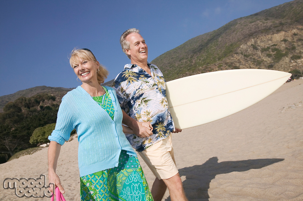 Smiling Couple with Surfboard on Beach