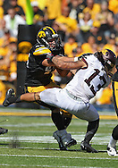 September 29 2012: Iowa Hawkeyes running back Mark Weisman (45) pushes off Minnesota Golden Gophers defensive back Derrick Wells (13) on a run during the third quarter of the NCAA football game between the Minnesota Golden Gophers and the Iowa Hawkeyes at Kinnick Stadium in Iowa City, Iowa on Saturday September 29, 2012. Iowa defeated Minnesota 31-13 to claim the Floyd of Rosedale Trophy.