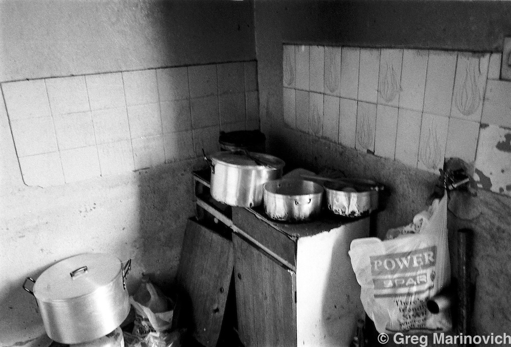 IPMG0113 South Africa, Ngwelezana 2000: . Dishes pile up in the kitchen of AIDS activist Deli Hlongwa in Ngwelezana in the KwaZulu Natal province of South Africa, March 25, 2000 on the day of her funeral.  Deli was a person living with full-blown AIDS who took part in the local `Funeral Campaign' where people with HIV and Aids tell others in the community of their disease and invite them to come look at them in their open casket when they die, to disprove the widely-held notion that HIV does not kill.  South Africa has a rapidly growing HIV crisis, with some 25% of ante-natal women testing positive..Photograph by Greg Marinovich/South Photographs
