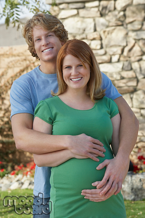 Expectant couple embracing in garden, portrait