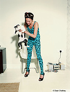 Betty wearing a bright patterned catsuit, holding her pet cat, Southend, UK 2006