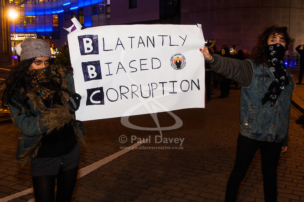 """London, December 23rd 2014. Online activism group Anonymous march through London from the City to the BBC's HQ on Great Portland Street in protest against alleged biases and coverups of a """"paedophile ring"""". PICTURED: Two young women parade a banner for the """"Blatantly Biased Corruption""""."""