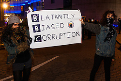 "London, December 23rd 2014. Online activism group Anonymous march through London from the City to the BBC's HQ on Great Portland Street in protest against alleged biases and coverups of a ""paedophile ring"". PICTURED: Two young women parade a banner for the ""Blatantly Biased Corruption""."