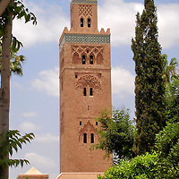 Koutoubia Mosque in Marrakech, Morocco<br /> The 253 foot, red sandstone minaret of the Koutoubia Mosque is not only the visual anchor of Jemaa el Fna but also Marrakech&rsquo;s most iconic landmark. The Bookseller&rsquo;s Mosque reflects the architectural style of the Almohad Dynasty. This Berber Muslim movement reigned over Morocco from 1121 through 1269. Shortly after seizing power in Marrakech in 1147, they destroyed the palace of their Almoravid predecessor and constructed their first mosque. This replacement was finished around 1190. The minaret features scalloped arches, two glazed pottery borders (faience) and is crowned with a gilded dome plus three orbs. Interestingly, each side of the tower has a different design.