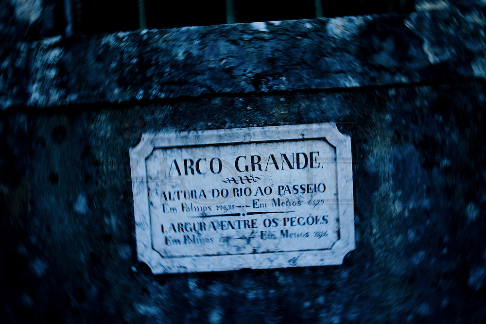 Plaque that marks the Arco Grande in the Aguas Livres aqueduct. Since its foundation, the city of Lisbon had problems with the supply of drinking water to the population. In order to solve this problem, in 1731 King John V begins the contruction of the long-touted &quot;Aguas Livres Aqueduct&quot; wich has its construction completed in 1748, from this moment Lisbon would have 3 times more water than previously available.<br /> The aqueduct extends over 14,174 meters and consists of 127 arches along its route. Of all the arches, the most known is the one in the valley of Alcantara, the Arco Grande, is 65 meters high and is the largest pointed arch in the world.<br /> The other reason that made the Aqueduct famous is to have been the stage of nineteenth century's most famous serial killer in Portugal, Diogo Alves. Born in Spain, came to live in Lisbon at a very early age, known as the &quot;Assassino do Aqueduto das Aguas Livres&quot; or also &quot;Pancadas&quot;. Diogo Alves is thought to have robbed and thrown from the Arco Grande area more than seventy people. No one ever found out how he got the key to enter the aqueduct and commit the crimes.<br /> Diogo Alves was convicted and hanged in 1841. His head was stored in formalin at the time so that medicine could studie his and be able to characterize the mind of a criminal.<br /> In 1911 is presented to the public the film &quot;Os crimes de Diogo Alves,&quot; the first Portuguese fictional film. 15/01/2012 NO SALES IN PORTUGAL