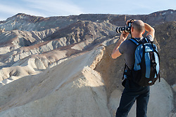 Photographer above eroded badlands and ravines, Twenty Mule Team Canyon, Death Valley National Park, California, USA
