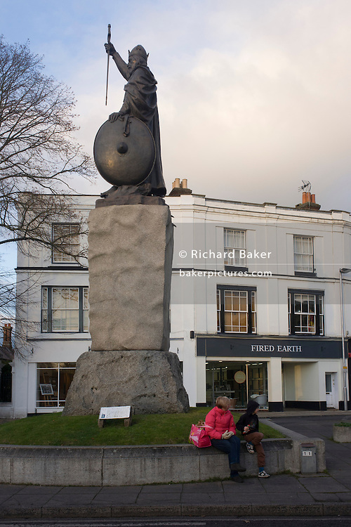 "A mother and son sit below the statue (by sculptor Hamo Thornycroft) of Saxon King Alfred that overlooks English citizens living in a modern Winchester, Hampshire, England. Alfred the Great (849 - 899) was King of Wessex from 871 to 899. Alfred successfully defended his kingdom against the Viking attempt at conquest, and by his death had become the dominant ruler in England. He is the only English monarch to be accorded the epithet ""the Great"". The Thornycroft statue was unveiled during the millenary celebrations of Alfred's death."