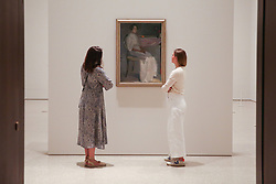 """© Licensed to London News Pictures. 17/07/2019. London, UK. Staff members view Helene Schjerfbeck's painting """"Costume Picture II 1909"""" at Royal Academy of Arts during the preview of her first ever exhibition in the UK. The exhibition features around 65 portraits, landscapes and still life, charting the development of Helene Schjerfbeck's work from a naturalistic style inspired by French Salon painters in the early 1880s, to a radically abstracted and modern approach from the turn of the twentieth century onwards. The exhibition runs  from 20 July to 27 October 2019. Photo credit: Dinendra Haria/LNP"""