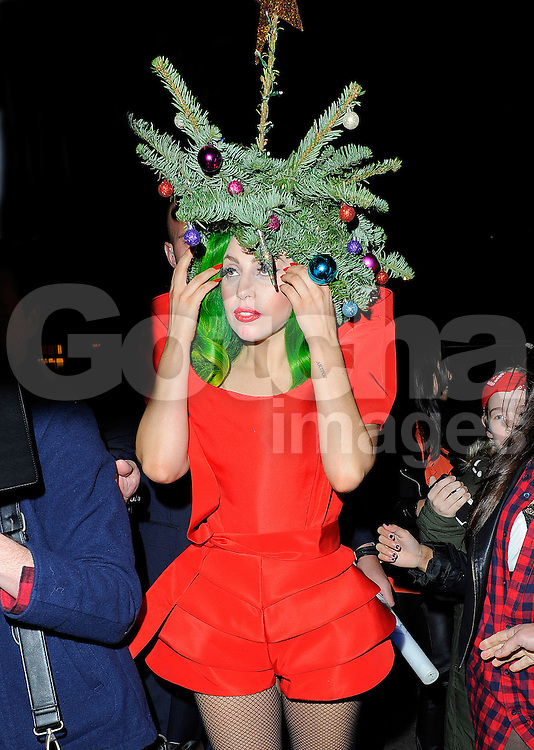 lady gaga wearing red dress and a christmas tree on her head as she arrives back
