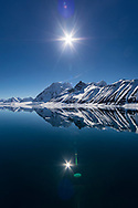 A reflection of the sun and  beautiful mountains  in the cold waters of Hornsund, Svalbard.