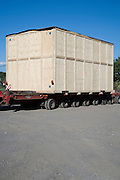 very large wooden box placed on a flatbed and waiting for transportation