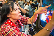 03 MARCH 2013 - BANGKOK, THAILAND: . A Pheu Thai supporter flips her middle fingers at a television set when it was announced on TV that MR Sukhumbhand Paribatra, the incumbent running on the Democrat ticket, had won the election for Bangkok governor. Pongsapat Pongchareon, running on the Pheu Thai ticket, lost the Bangkok's Governor's race to MR Sukhumbhand Paribatra, the incumbent running on the Democrat ticket. Sukhumbhand won the race after scoring a record number of votes, more than 1.2 million to Pongsapat's 1 million. The results were seen as an upset even though Sukhumbhand was the incumbent because all of the pre-election polls and the exit polls conducted on election day showed Patsapong winning.    PHOTO BY JACK KURTZ